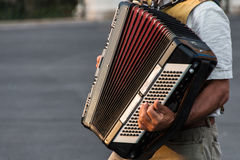 Street musician playing an accordion. For alms at sunset in Syracuse, Ortigia, Sicily, Italy Royalty Free Stock Photo