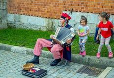 Street musician, playing accordion, entertaining children. Krakow/Poland- August 14, 2017: Wawel Royal Castle, street musician – man, wearing traditional Royalty Free Stock Images