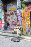 Street musician playing guitar in laneway Stock Image
