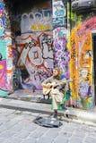 Street musician playing guitar in laneway Stock Image