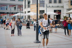 Street musician playing guitar live. SOPOT, POLAND - SEPTEMBER 10 2016: Street musician playing guitar live on the streets of a seaside resort town in Eastern Royalty Free Stock Image