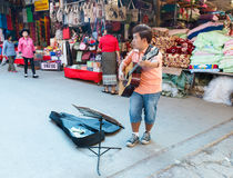 Street musician playing guitar at local market. Stock Images