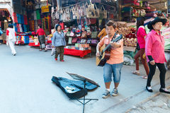 Street musician playing guitar at local market. Stock Photo