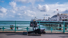 A street musician playing guitar and singing. With Brighton pier and the sea in the background Royalty Free Stock Images