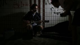 A street musician playing on guitar in the underpass. Vagrant lifestyle. Playing in the underpass to make a living. Unemployed mus. Ician. Future rock star. One