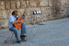 Street musician is playing on his flamenco guitar. stock photos