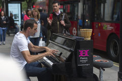 Street musician. Playing piano on Bond street, London Royalty Free Stock Photo