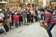 Street musician playing the sax in front of a crowd in Florence , Italy