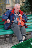 A street musician playing the violin. Street musician plays the violin on the bench of the Park earning a living Stock Image