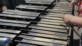 A street musician plays on a metallophone. A street musician plays with chopsticks on a metallophone stock video footage