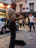 Street musician plays soprano saxophone on Paris sidewalk Stock Images