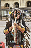 Street musician Red Indians. Turin, Italy - April 27, 2013: Red indian in traditional costume plays in the center of Turin, Italy. Street performance of a group Royalty Free Stock Photography