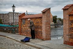 Street musician with saxophone on pedestrian Tumski Bridge  over Oder river to Ostrow Tumski island in Wroclaw city Stock Images