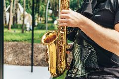 Street musician saxophonist plays jazz music in park in sunny day. Selective focus on hands and saxophone, copy space Stock Images