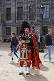 Street musician with Scottish traditional bagpipes stock photography
