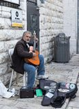 Street musician sits on the street and plays the guitar in the old city of Jerusalem, Israel stock photo