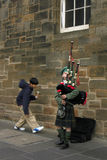 Street musician - young bagpiper in Edinburgh. Little busker - bagpiper boy in traditional Scottish dress on the street of Edinburgh, Scotland royalty free stock image