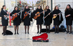 Street Musicians. Group of seven female musicians dressed in black playing music with guitars,mandolin and flute in the Royalty Free Stock Photos
