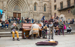 Street musicians at Barcelona cathedral. Three street musicians play for a few coins in front of the cathedral of Barcelona with a crowd watching them Royalty Free Stock Image