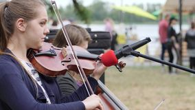 Street musicians earn cash playing on cello and violin, artists perform musical composition for passersby, stock footage