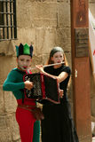 Street musicians in harlequin costumes. Stock Photo