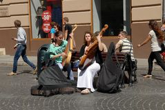 Street musicians. Lvov, Ukraine - July 22, 2016: Street musicians on Market Square, one of the most famous and busiest shopping square in Ukraine. Girls playing Royalty Free Stock Image