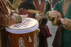 Street musicians in national costumes play folk instruments - a drum and a dombra during. A holiday stock photography