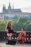 Street musicians perform with Prague Castel on background Royalty Free Stock Image