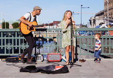 Street musicians. Stockholm, Sweden - August 19, 2015: Two street musicians on the bridge Stallbron in Stockholm with an interested little boy from the audience Royalty Free Stock Images