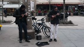 Street musicians. Two guys dresed like urban blues brothers playing guitars on the street in Zagreb, Croatia stock video