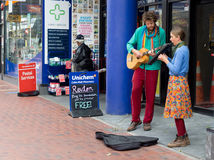 Street Musicians. Wellington, New Zealand - February 10, 2017: Street musician playing at Cuba Mall pedestrian street Royalty Free Stock Image