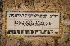 Street name plaque in the Old City of Jerusalem, Israel. Armenian Orthodox Patriarchate st., street name plaque written in three languages: Hebrew, Arabic and royalty free stock image