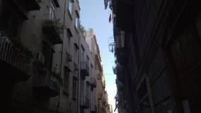 A street in Naples. A narrow street in Naples, Italy. We can first see top of houses with drying clothes on a rope,  then a pavement with parked scooters stock footage