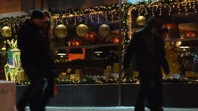 Street at night in the city with the Christmas decoration of the windows on the background of people walking. Russia, Novosibirsk. Vogzalnaya magistral 14-12 stock video footage