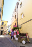 Street in Olbia, Sardinia, Italy. Olbia, Italy - August 24, 2016: Street of the old town of Olbia with mannequins in a clothing store, bar terraces and people Stock Photos