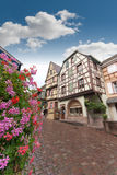Street in old Alsace town, Riquewihr. Cobbled street in Alsace town with half timbered houses and flowers, Riquewihr Stock Photos