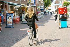 Street of old city. Dorpstraat. A girl rides a bicycle along the street of the old city Dorpstraat. 30 August 2018. Zoetermeer. Netherlands stock photography