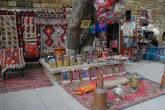 Street of the old city with traditional Azerbaijani carpets on the wall and the seller stock photography