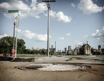 A street in the old Detroit neighborhood. Distressed Detroit neihborhood with many abandoned houses. Downtown skysrapers in the backdrop royalty free stock photo