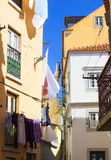 Street with old houses and hanged clothes. Lisbon Royalty Free Stock Photography