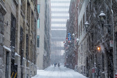 Street of Old-Montreal in winter under a snow storm with a modern skyscraper in the background Stock Image