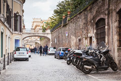 Street in old Rome with parked cars and motorcycles Royalty Free Stock Images