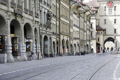 Street of old town in Bern. Bern, Switzerland - April 17, 2017: Decorative historic buildings and arcades along a cobbled street with visible tram rails and in Royalty Free Stock Photos