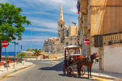 Street in old town of Valletta, Malta. Horse carriage on the street of old town and St. Paul`s Anglican Pro-Cathedral in Valletta, Malta Stock Images