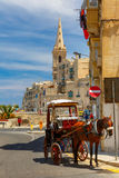 Street in old town of Valletta, Malta. Horse carriage on the street of old town and St. Paul`s Anglican Pro-Cathedral in Valletta, Malta Stock Photo