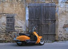 Street in old village with wood door and old scooter Stock Image
