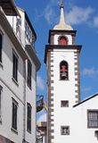 Street of old white painted houses and the tower of the historic parish church of saint peters in funchal madeira. A street of old white painted houses and the royalty free stock image