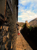 Street in Ollantaytambo, Peru. A girl dressed in traditional costume walks through the streets of ancient Ollantaytambo located in Peru Royalty Free Stock Image