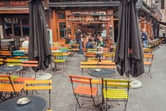 Street with outdoor cafe, talking people and old buildings of historical city with restaurants Stock Photos