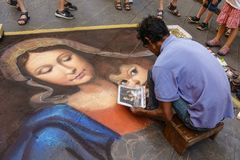 Street painter. The artist paints a religious colorful picture of madonna, virgin Mary and child Christ on a street, with chalk on the asphalt, people watching Royalty Free Stock Images